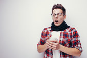 Man with flu and fever wrapped holding cup of healing