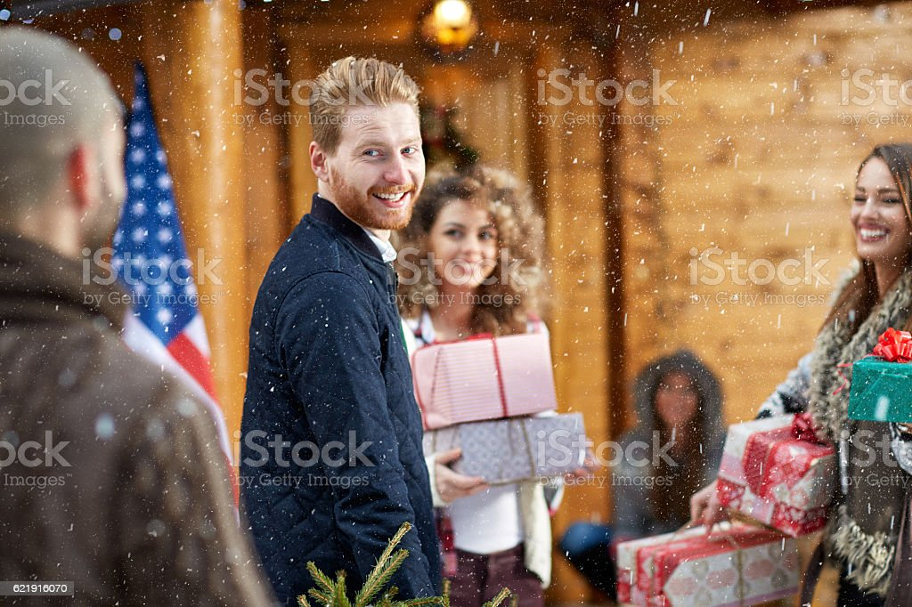 Man with friends bringing gifts for Christmas stock photo