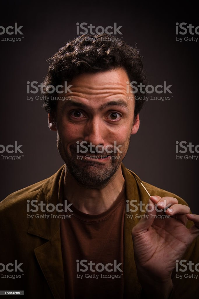 Man with funny face and toothpick in hand stock photo