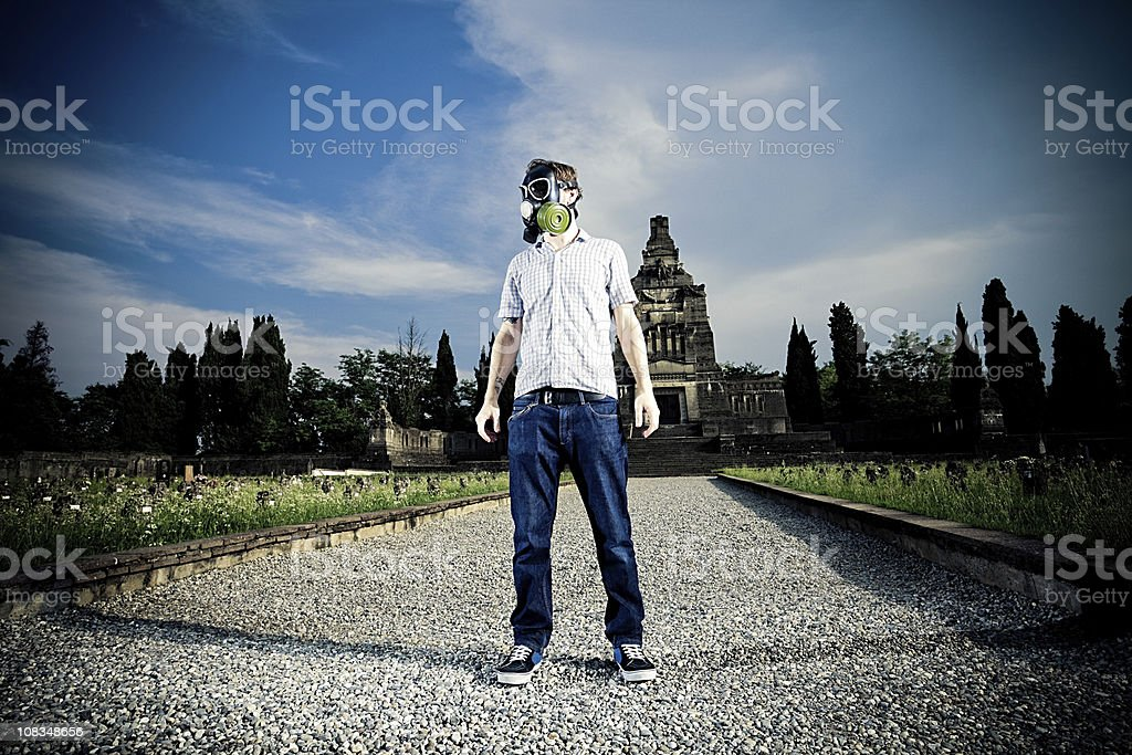 Man with gas mask in a cemetery stock photo
