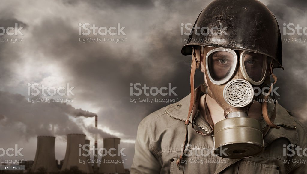 Man with gas mask in polluted industrial landscape royalty-free stock photo