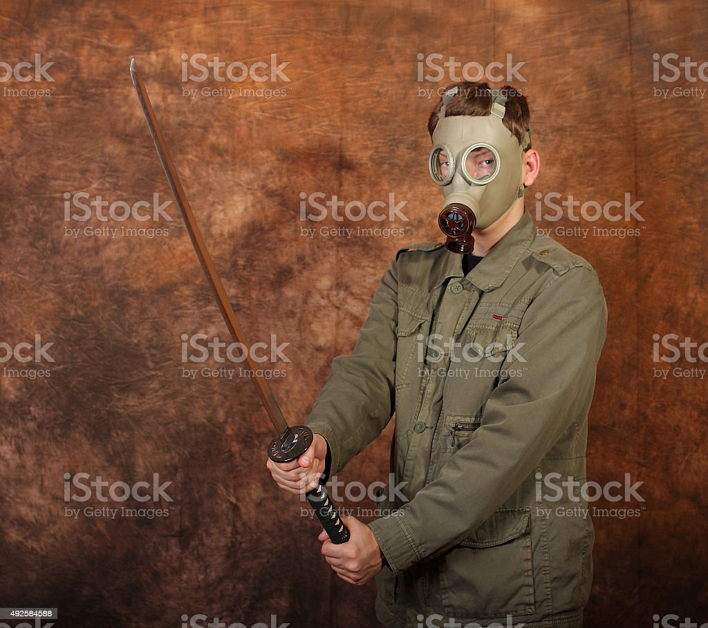 Man with gas mask, katana sword on brown batik  background stock photo
