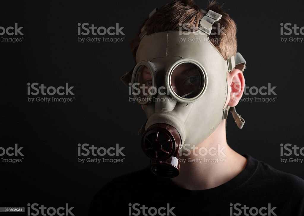Man with gas mask on black  background stock photo