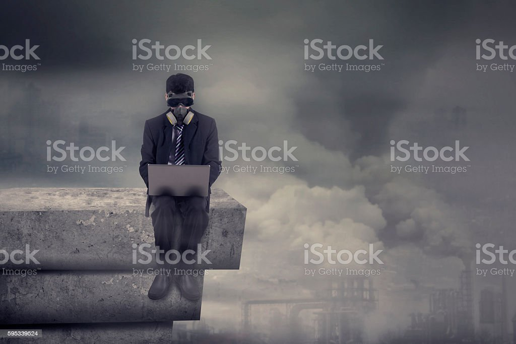 Man with gas mask uses laptop on rooftop stock photo