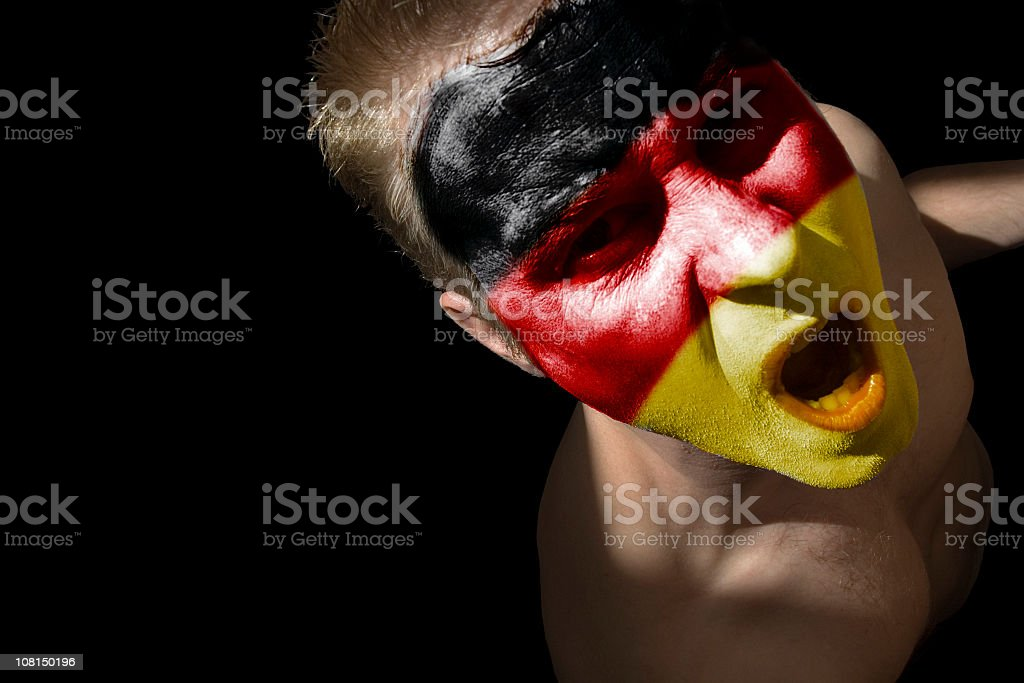 Man with German Flag Colors Painted Face, Isolated on Black stock photo