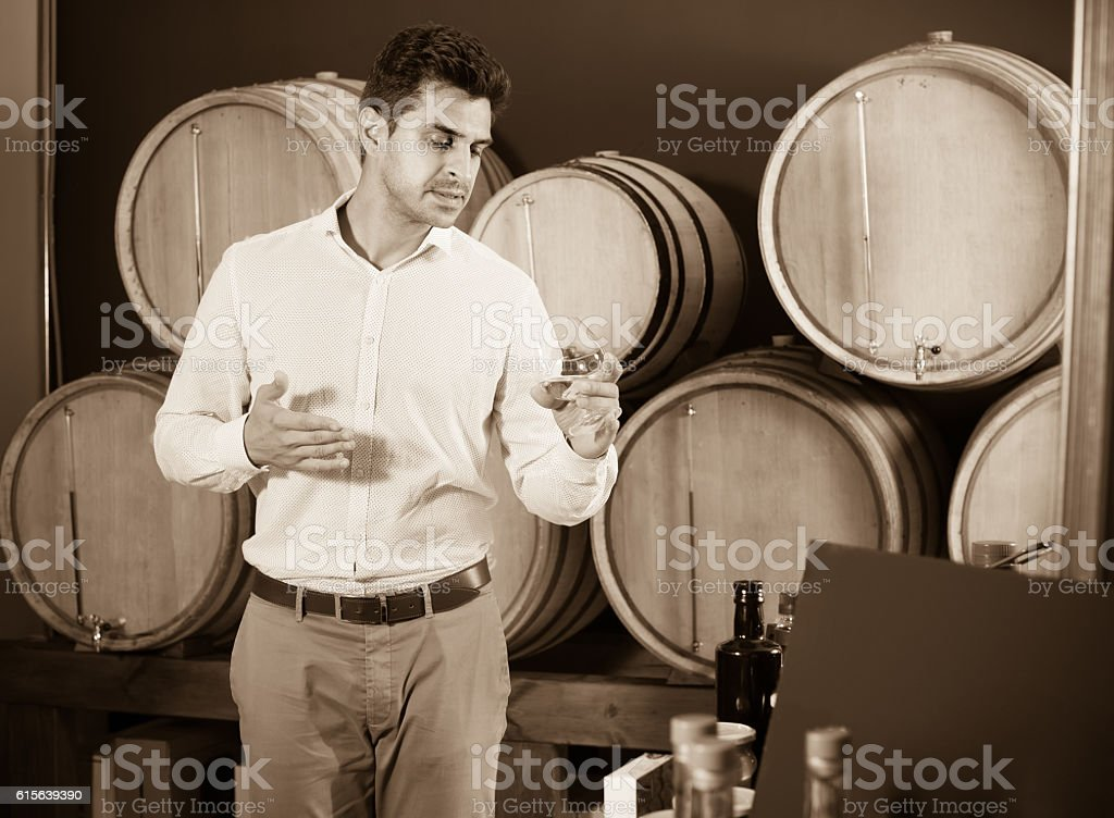 man with glass of brandy in winery store stock photo