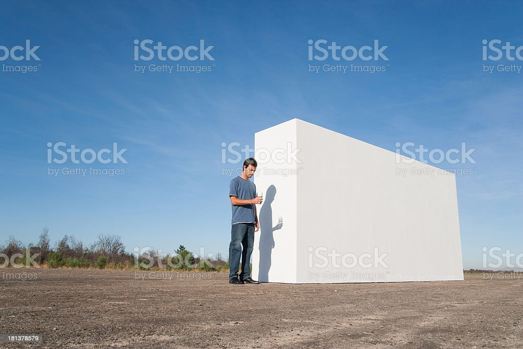 Man with glass of water standing beside white wall royalty-free stock photo