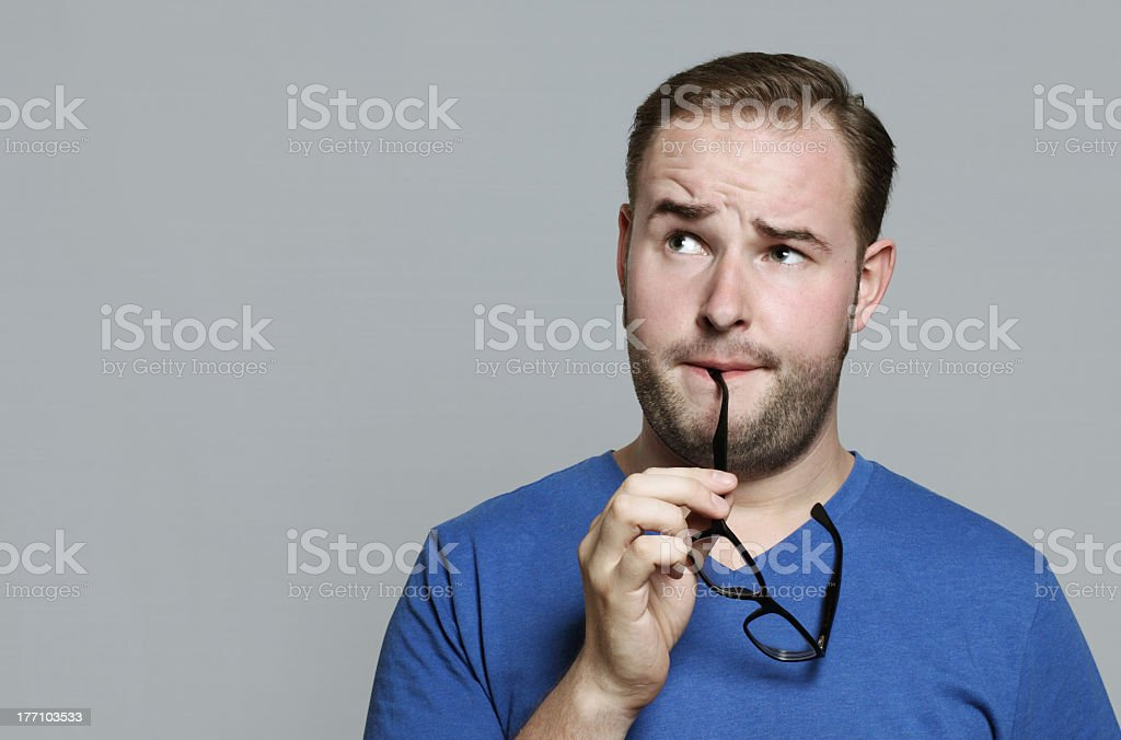 Man with glasses arm in mouth and a contemplative look royalty-free stock photo