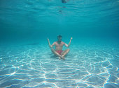 Man with glasses in the lotus position meditating under water