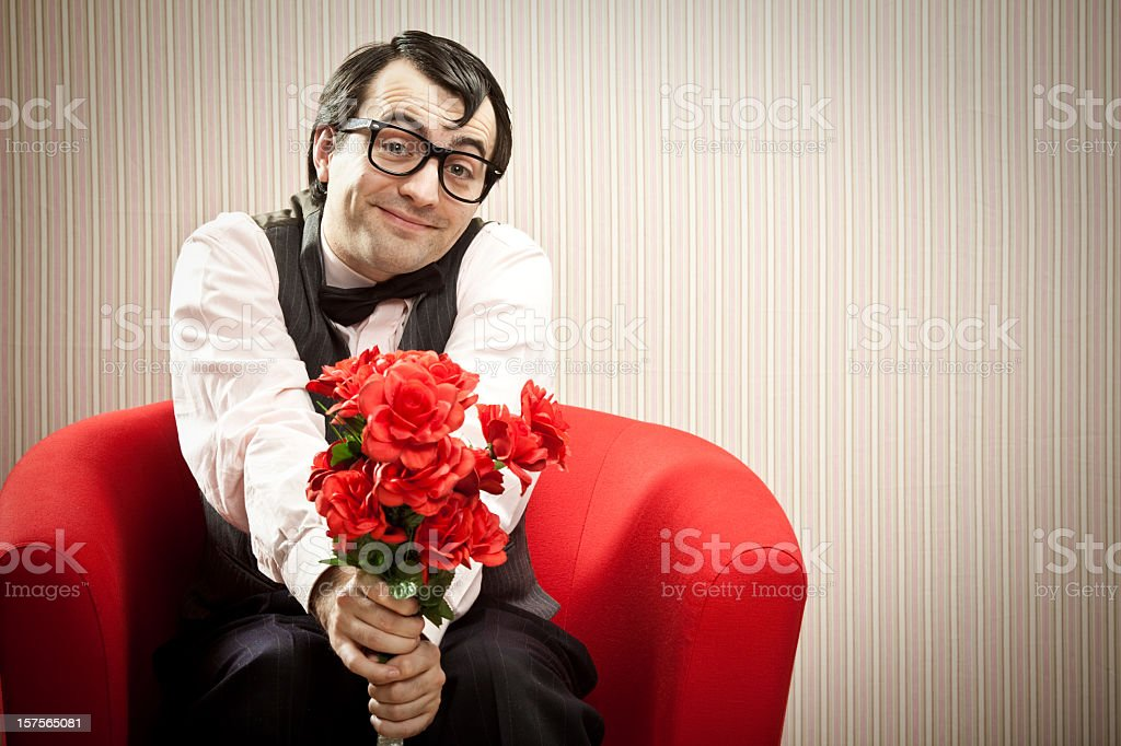 Man with glasses sitting on a red chair extending flowers stock photo