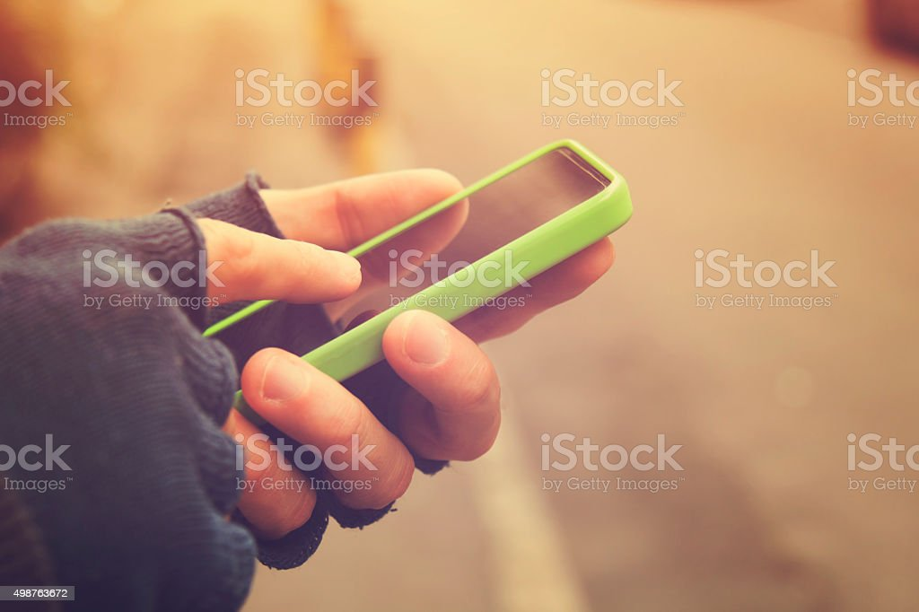 Man with gloves using cellphone outdoors. stock photo