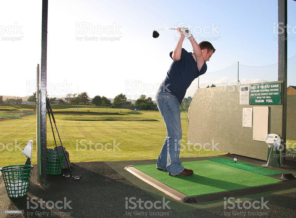 Man with golfing pose on golf range royalty-free stock photo