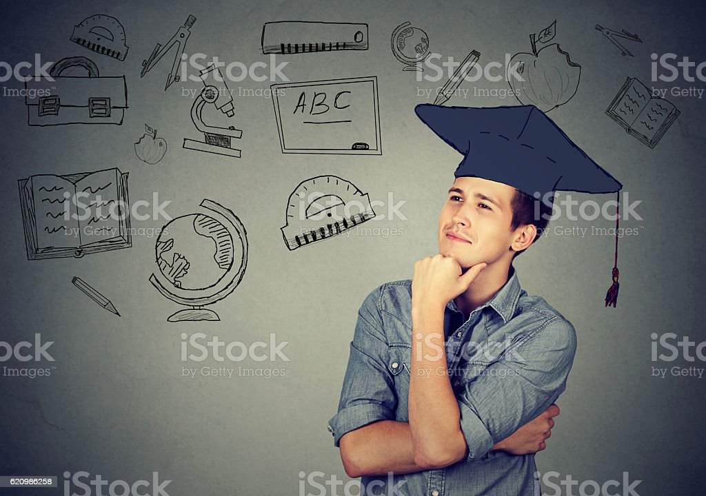man with graduation hat looking up thinking stock photo