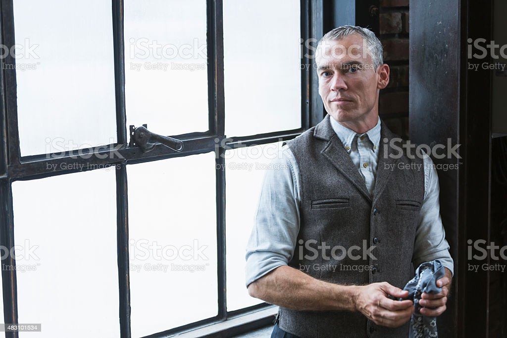 Man with gray hair sitting by window in old building stock photo