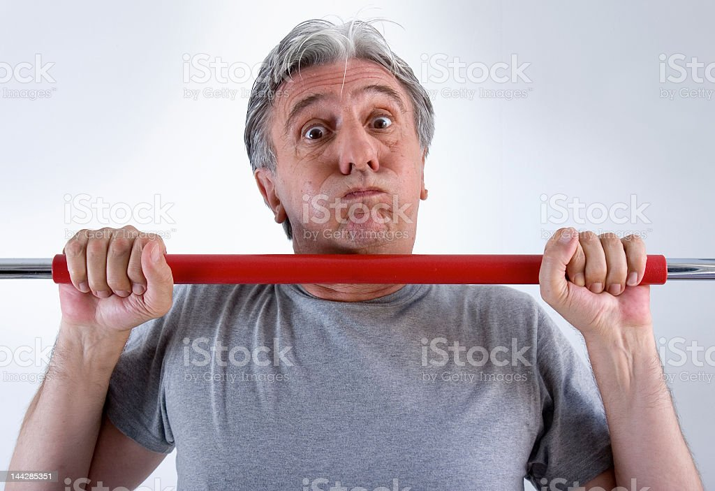 Man with gray hair working out with red weights stock photo