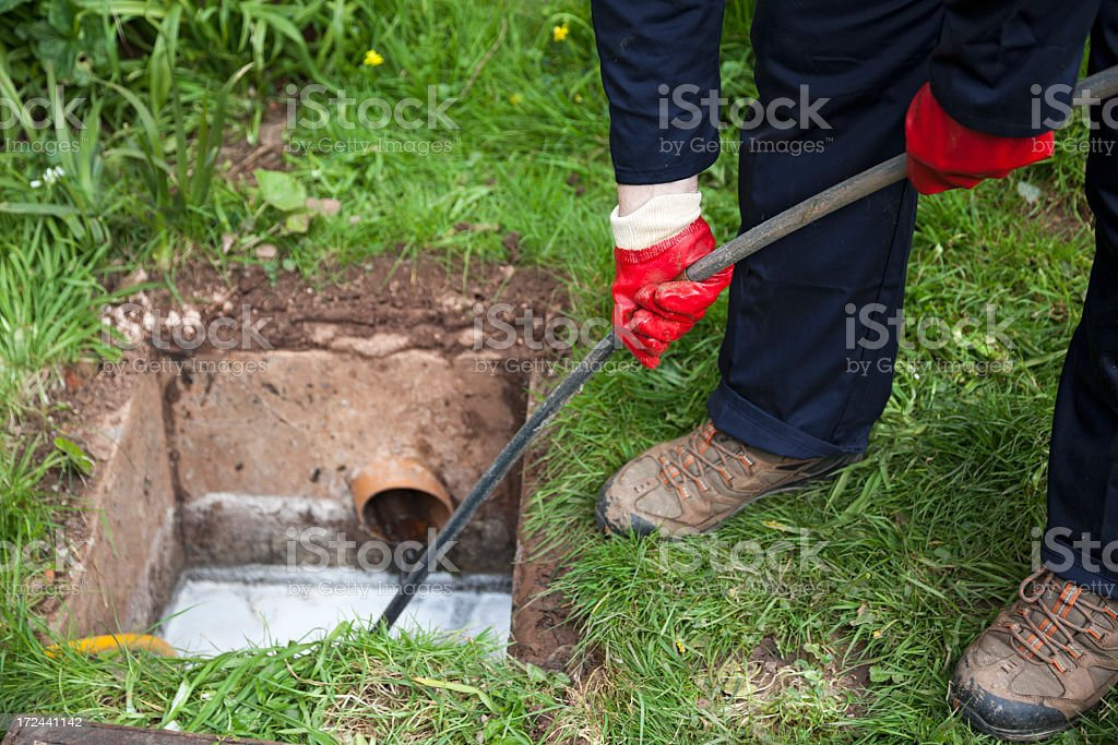 Man with ground open unblocking a drain with a tool stock photo