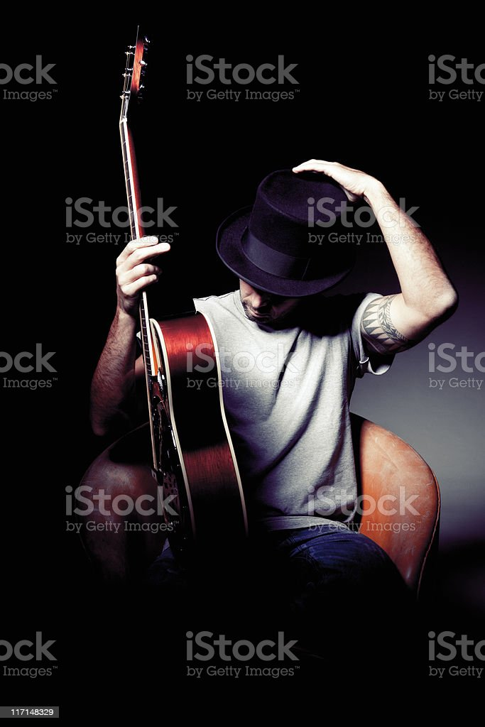 Man with guitar adjusting top hat royalty-free stock photo