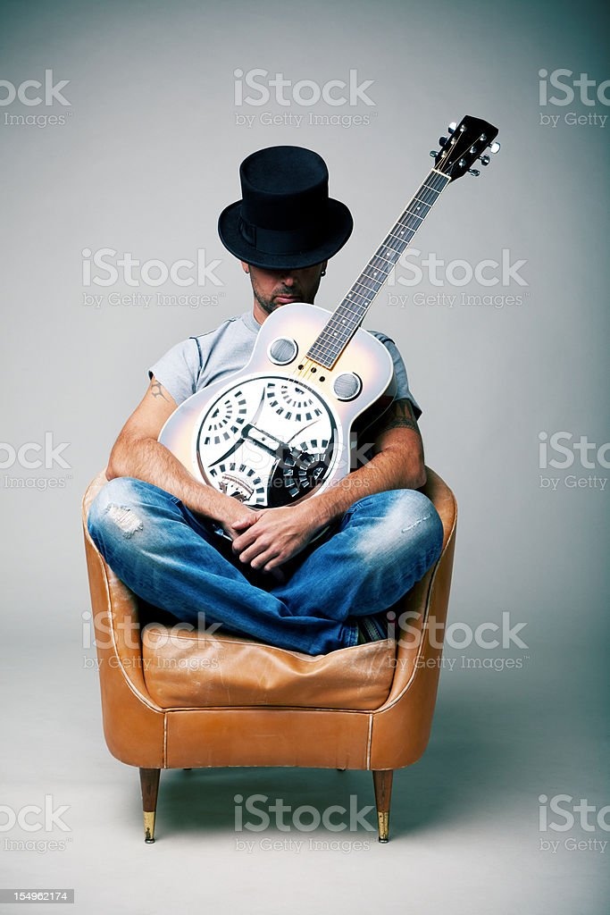 Man with guitar sitting on armchair stock photo