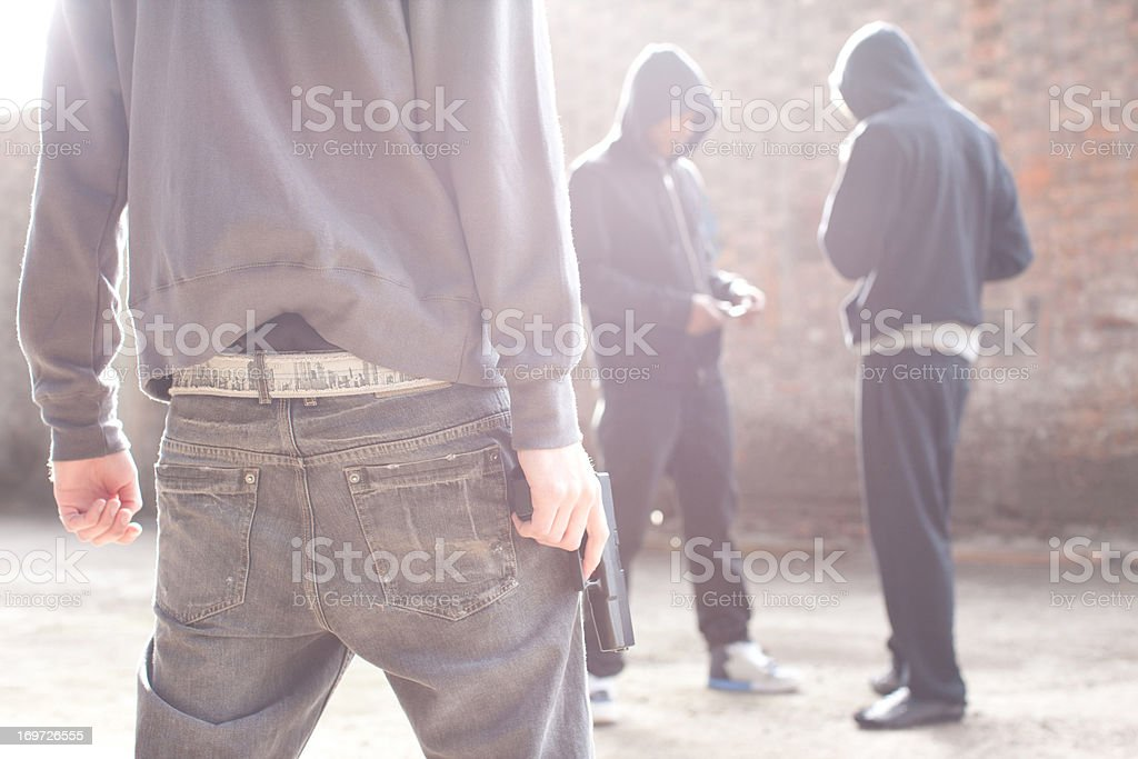 Man with gun approaching drug dealers royalty-free stock photo