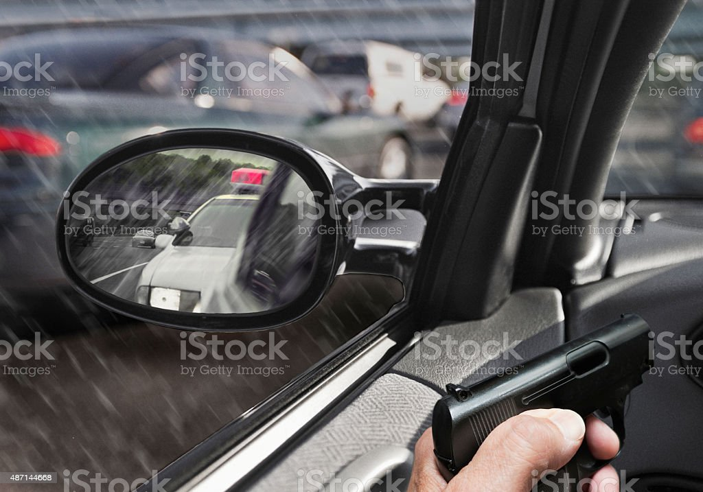 man with gun in car with police car in sideview mirror stock photo
