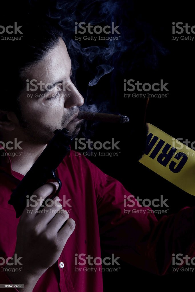 Man with gun lighting up cigar via burnt cordon tape stock photo