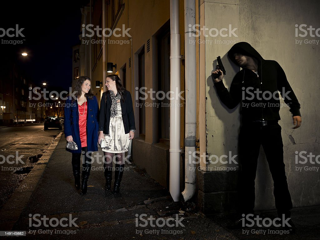 Man with gun stalking two young women stock photo