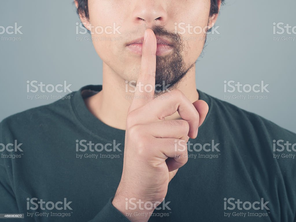 Man with half beard and finger on lips stock photo