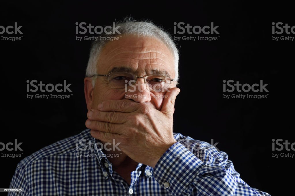Man with hand in mouth on black stock photo
