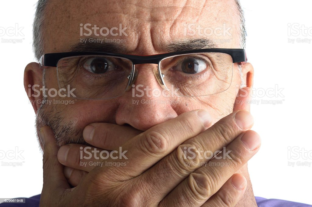 Man with hand in mouth stock photo