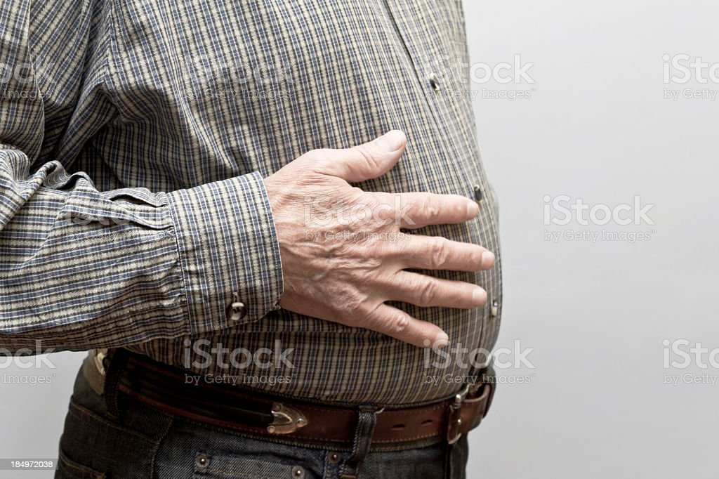 Man with hand on his stomach to depict indigestion stock photo