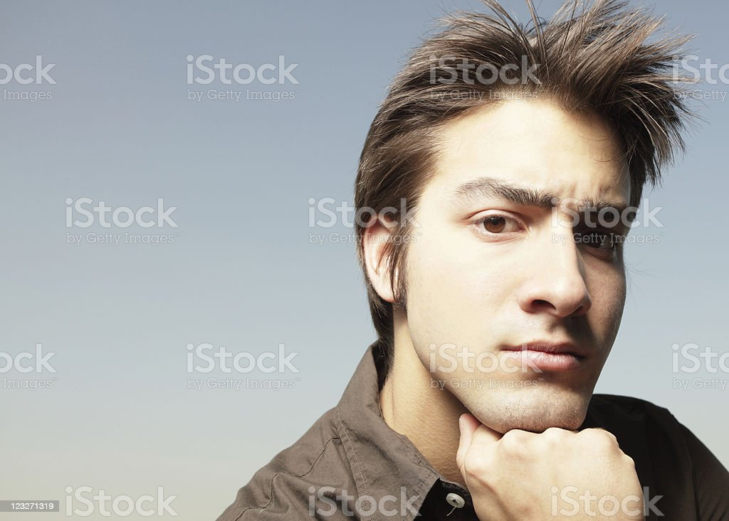 Man with hand under chin stock photo