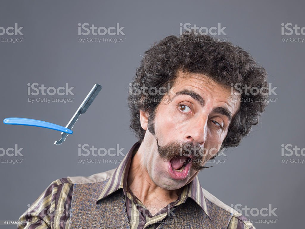 Man with handle bar mustache confronting flying razor stock photo