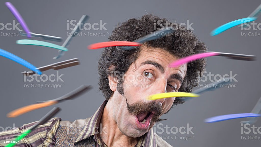 Man with handle bar mustache confronting flying razors stock photo