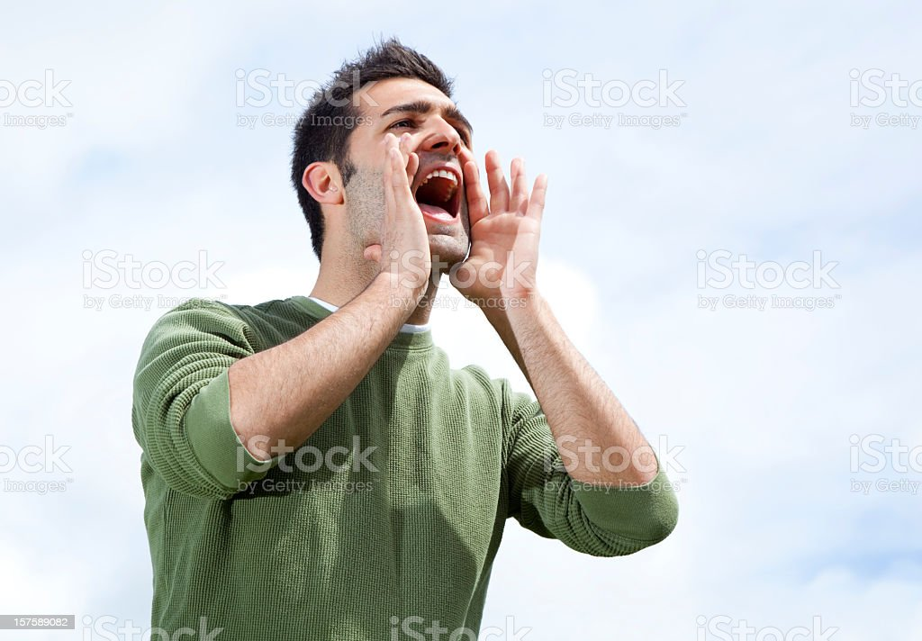 Man with hands around mouth to shout in distance stock photo