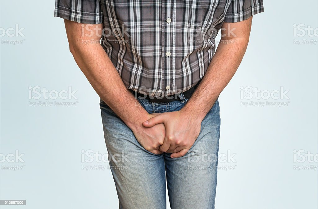 Man with hands holding his crotch, he wants to pee stock photo