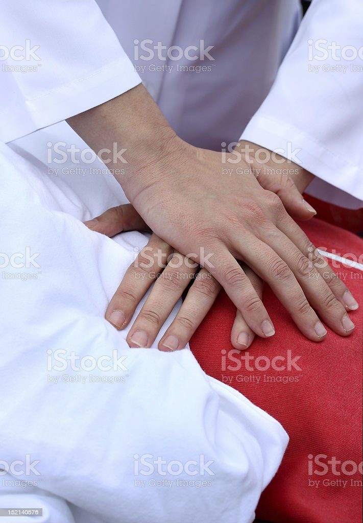 A man with hands on a dummy's chest learning CPR royalty-free stock photo