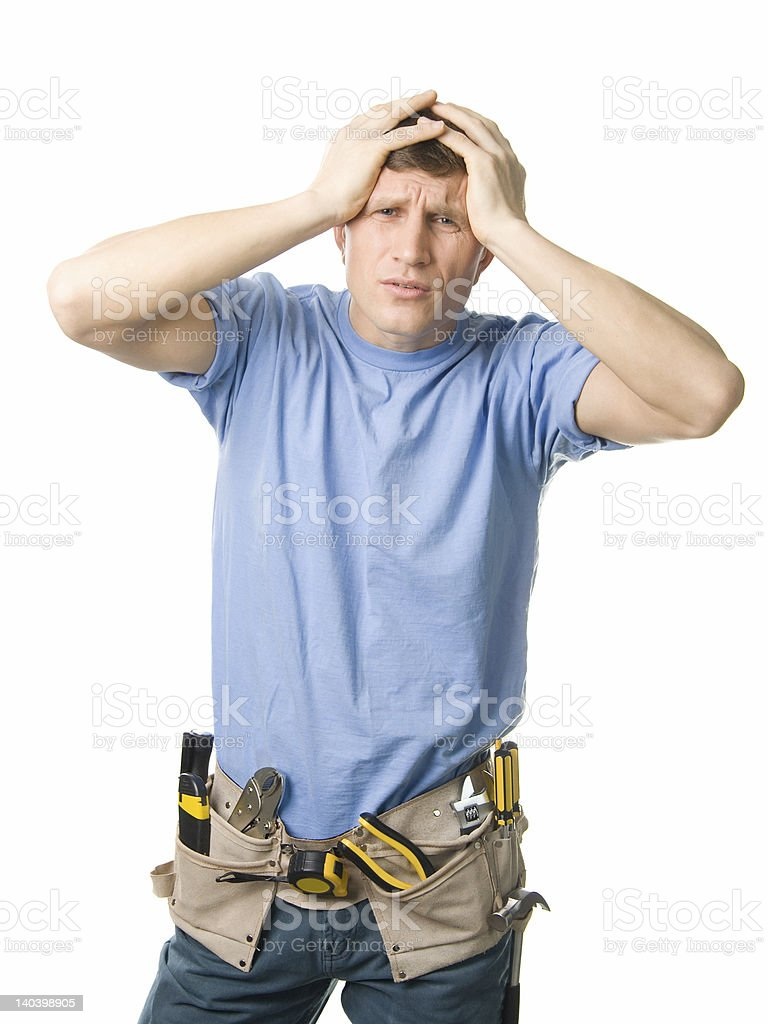 Man with hands on head wearing a tool belt royalty-free stock photo