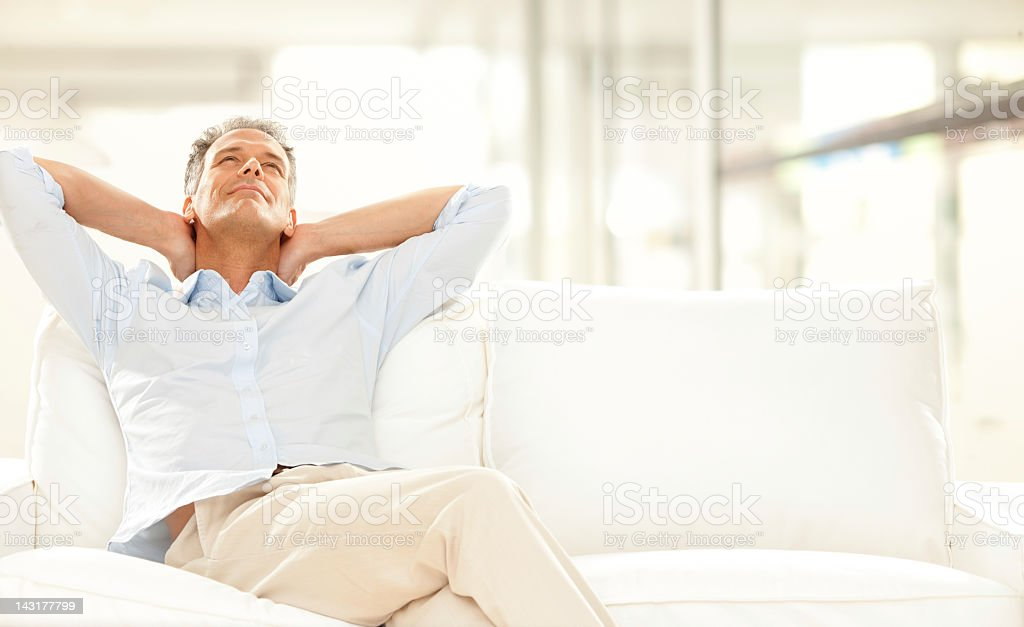 Man with hands on his neck, relaxing on white sofa stock photo