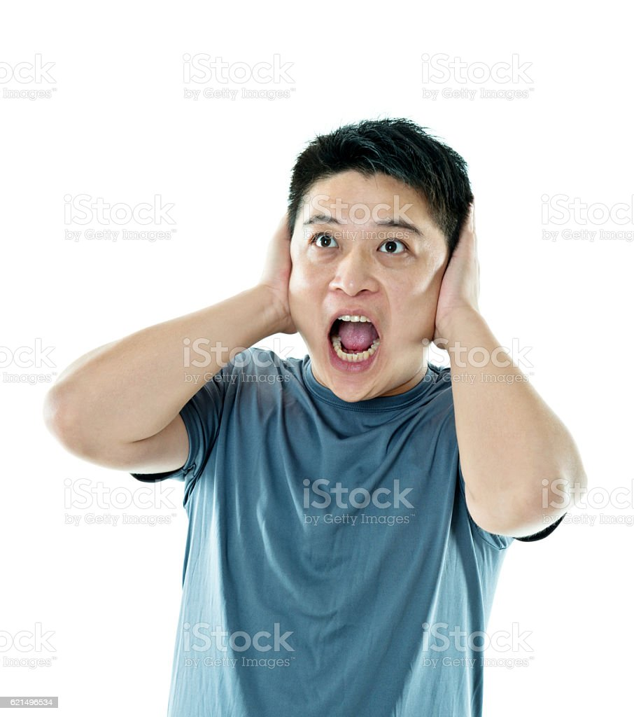 Man with hands over ears stock photo