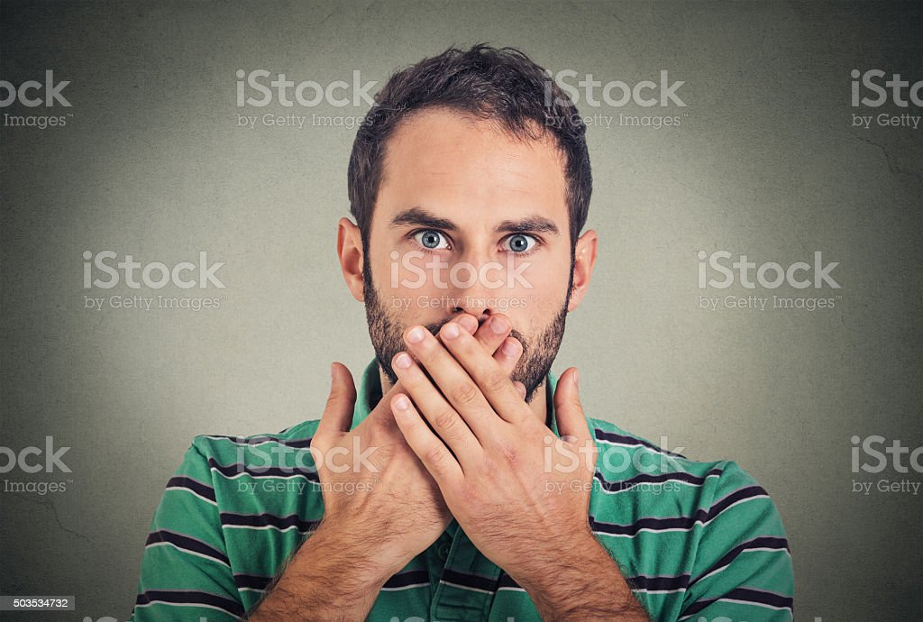 man with hands over his mouth, speechless stock photo