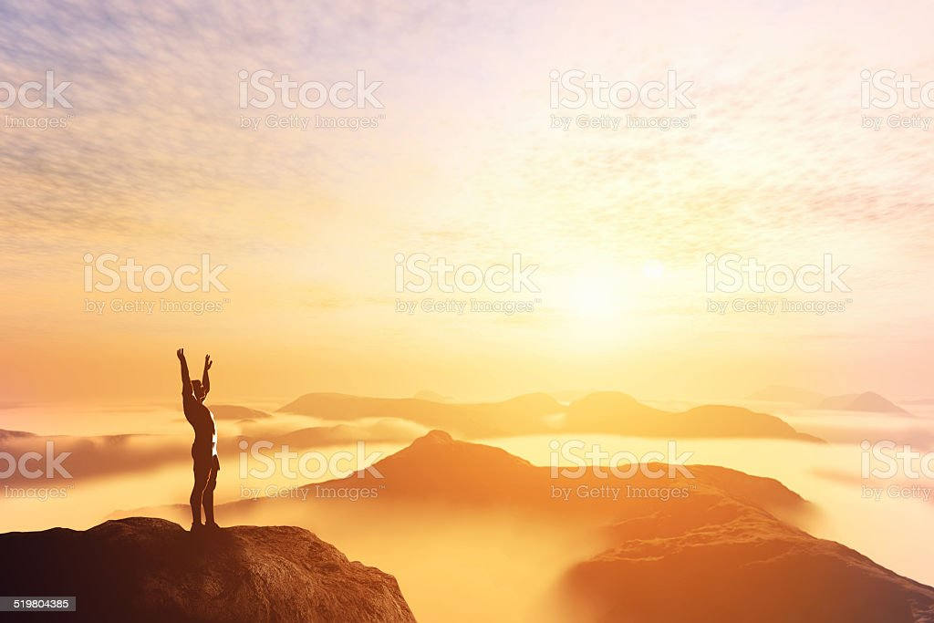 Man with hands up on the top of a mountain stock photo