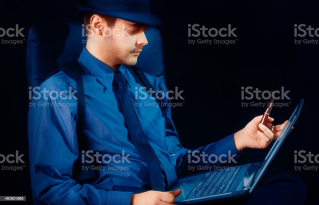Man with Hat and Pipe Looking at Laptop royalty-free stock photo