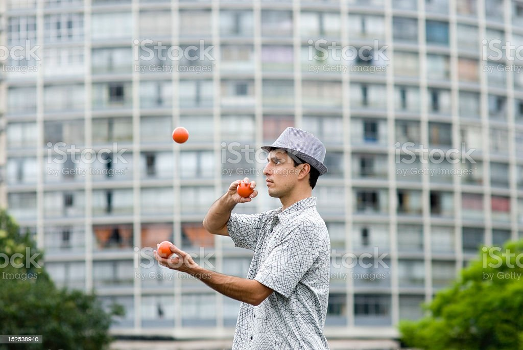 Man with hat in an urban park juggling orange balls stock photo