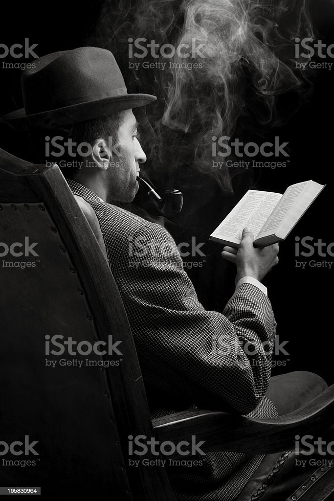 Man with hat reading book while smoking pipe in dark stock photo