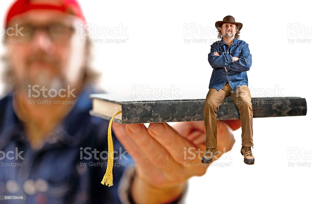 man with hat sitting on the book stock photo
