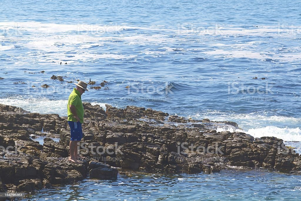 Man with Hat Standing By Rock Pool and Sea stock photo