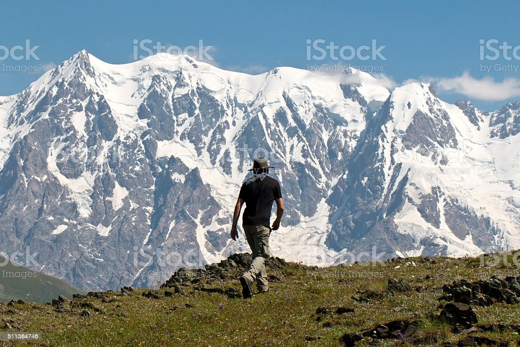 man with hat walking on the range Caucasus stock photo