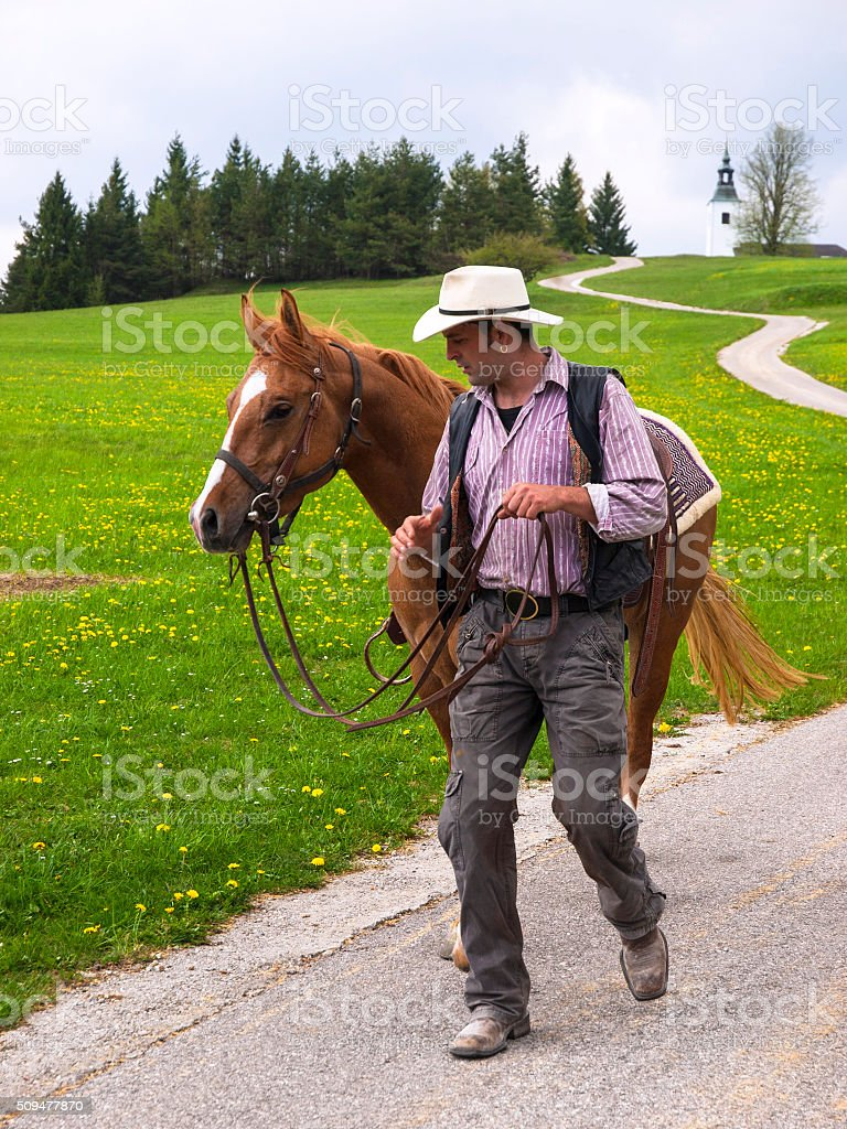 Man with hat walking the horse on country road stock photo