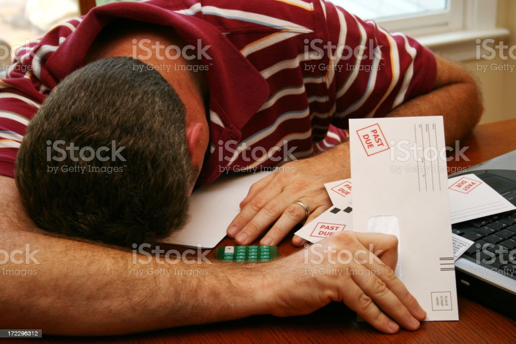 Man with head face down on his desk holding past due bills stock photo