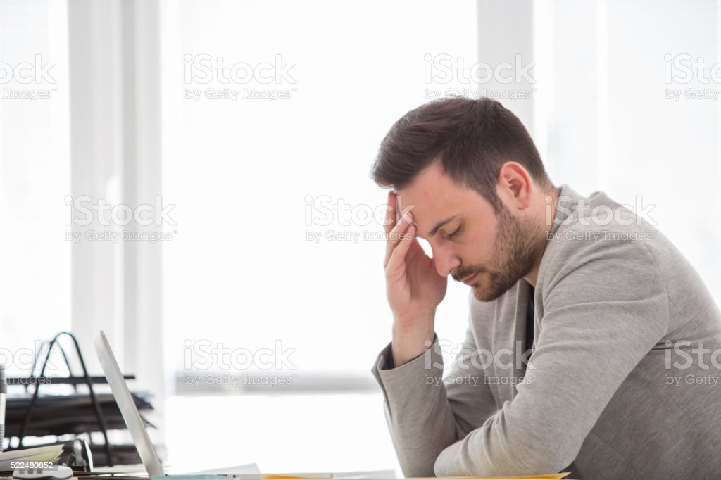 Man with headache at office stock photo